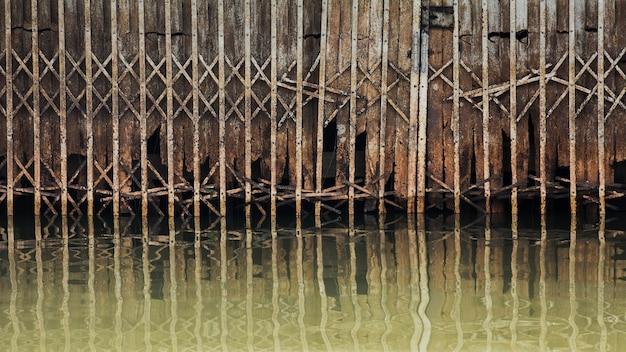 Arrugginito e danno della porta di metallo antico scorrevole nell'acqua