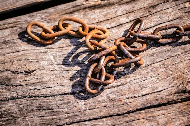 Catena di ferro arrugginita su uno sfondo di legno