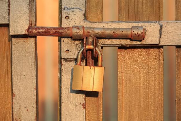 La serratura di metallo arrugginita e un bullone con vernice scrostata bloccano il vecchio cancello illuminato dal sole al tramonto