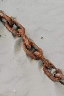 Vecchia catena di ancoraggio arrugginita abbandonata sulla spiaggia