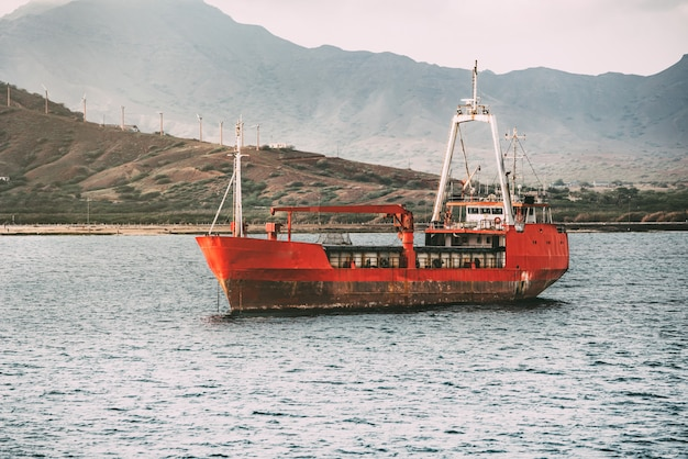 Vecchia barca arrugginita nella mescolanza del mare