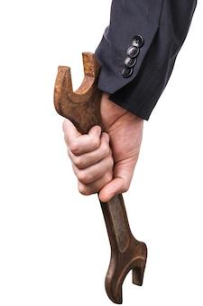 Chiave arrugginita in mano isolata su un concetto di superficie bianca sul tema della criminalità in ufficio