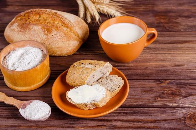 Pane di segale con panino cremoso piccolo su un piatto e una tazza di latte su una superficie di legno