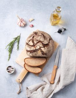 Pane di segale affettato su una tavola di legno con rosmarino, aglio e olio d'oliva