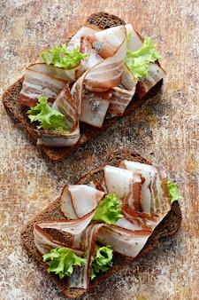 Pane tostato di segale con fette di pancetta (pancetta, lardo), aglio ed erbe italiane, antipasti, bruschette italiane (crostini)