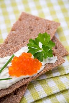 Fette biscottate di segale con formaggio morbido alle erbe e pancetta.