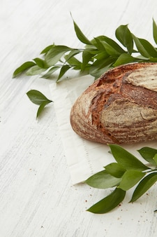 Pane biologico di segale con rami di foglie su un tavolo bianco