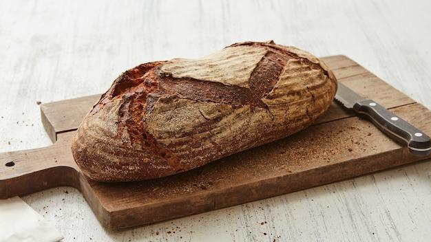 Pane ovale di segale su un tagliere con un coltello su sfondo bianco