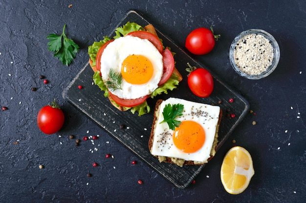 Toast di segale con purè di avocado, uovo fritto, pomodoro fresco, erbe aromatiche. gustosa colazione nutrizione appropriata. panino con uovo. la vista dall'alto