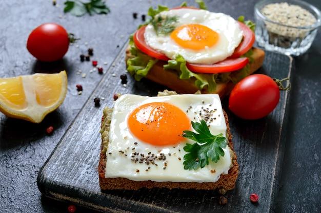 Toast di segale con purè di avocado, uovo fritto, pomodoro fresco, erbe aromatiche. gustosa colazione nutrizione appropriata. panino con uovo.