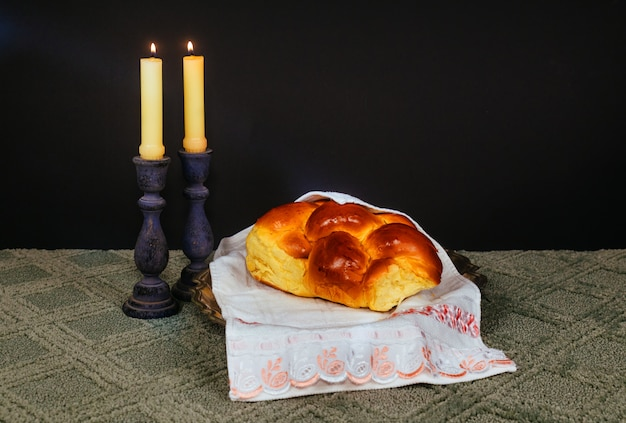 Immagine del sabato. challah pane, candele sul tavolo di legno. sovrapposizione di glitter