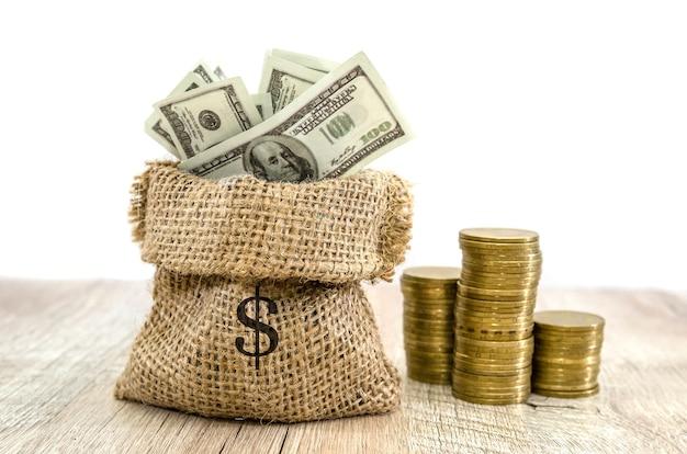 Sacco con il simbolo del dollaro su di esso con dollari e pile di monete su un tavolo di legno