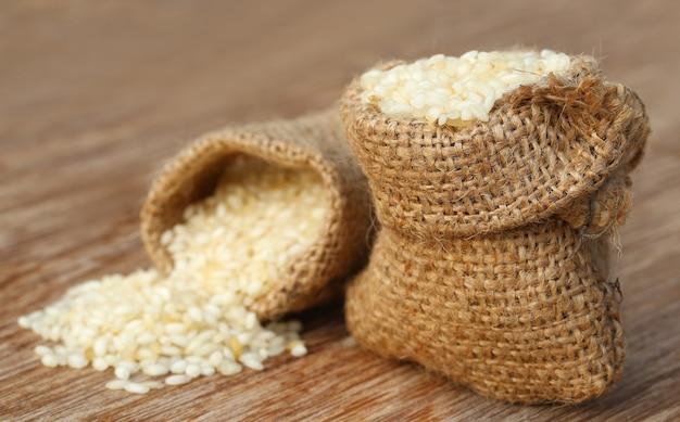 Sacco con riso sparso su superficie di legno