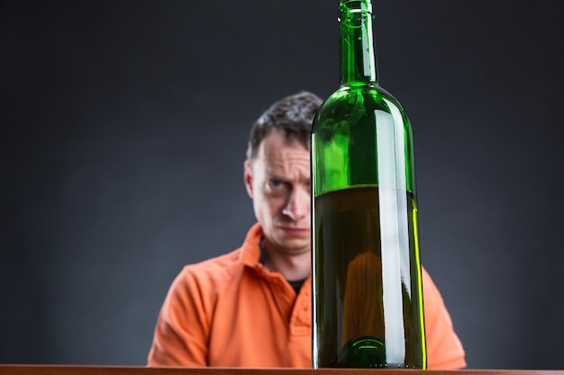 Il tossicodipendente triste guarda la bottiglia