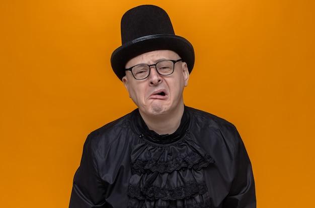 Uomo adulto triste con cappello a cilindro e occhiali in camicia gotica nera alla ricerca