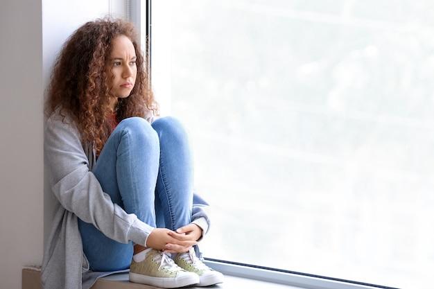 Triste donna afro-americana seduta sul davanzale della finestra. stop al razzismo