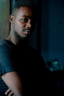 Triste uomo africano in piedi in camera oscura. concetto di disturbo d'ansia e depressione