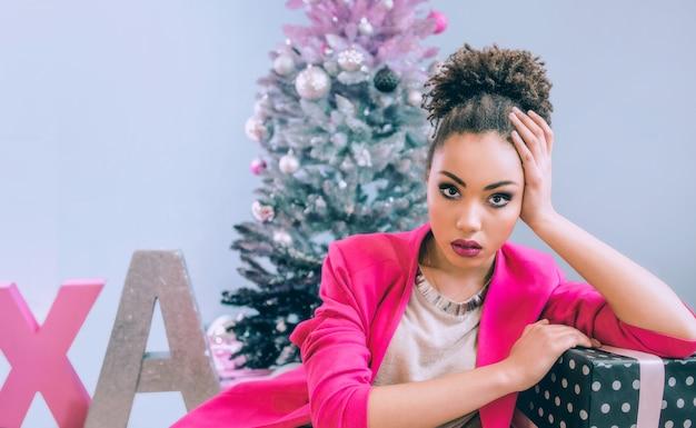 Triste donna afroamericana vicino all'albero di natale delusa dal regalo di natale