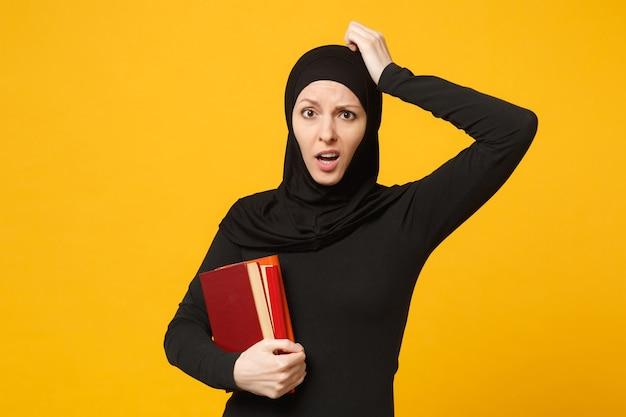 La ragazza studentessa musulmana araba triste in vestiti neri di hijab tiene i libri isolati sul ritratto giallo della parete. stile di vita religioso della gente, educazione nel concetto di scuola superiore. .