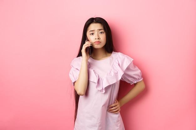 Ragazza asiatica triste che chiama qualcuno, tenendo il telefono e parlando, in piedi sconvolto su sfondo rosa.
