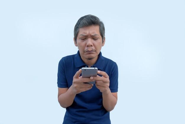 Uomo asiatico triste che guarda lo schermo del telefono