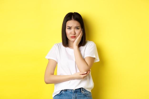 Triste donna asiatica che tocca la guancia e si acciglia, ha mal di denti, ha bisogno di vedere il dentista, in piedi cupa su sfondo giallo.