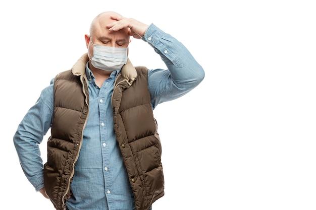 L'uomo adulto calvo triste in una mascherina medica sta tenendo la sua testa con la sua mano. precauzioni messe in quarantena per il periodo della pandemia di coronvirus. isolato su un muro bianco spazio per il testo.
