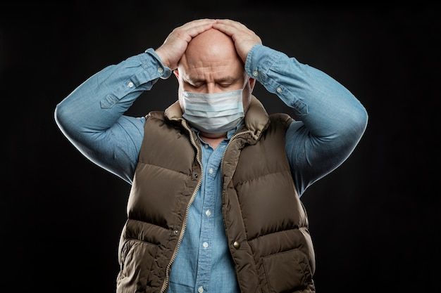 Triste uomo calvo adulto in una maschera medica sta tenendo la testa con le mani. precauzioni messe in quarantena per il periodo della pandemia di coronavirus. disoccupazione in una crisi globale.