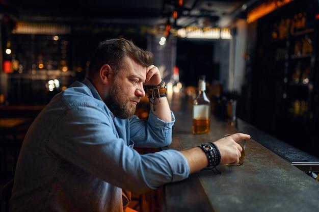 Uomo barbuto triste seduto al bancone del bar. una persona di sesso maschile arrabbiata in un pub, emozioni umane e attività ricreative, depressione, sollievo dallo stress