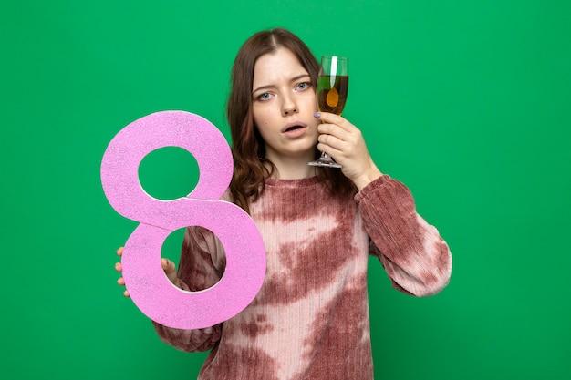 Triste bella ragazza sulla felice festa della donna che tiene il numero otto con un bicchiere di champagne intorno al viso