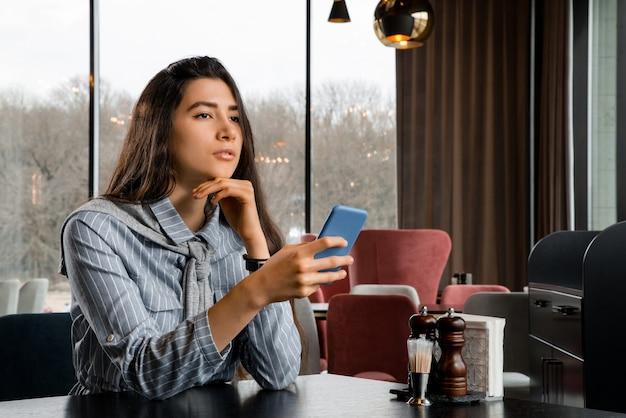 Triste bella giovane donna con lo smartphone in attesa del fidanzato nel ristorante