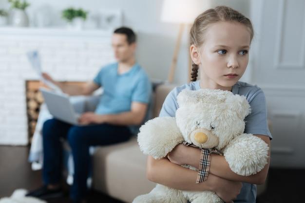 Bambina bionda dagli occhi azzurri triste che tiene il suo giocattolo e in piedi nella stanza mentre il suo papà lavora in background