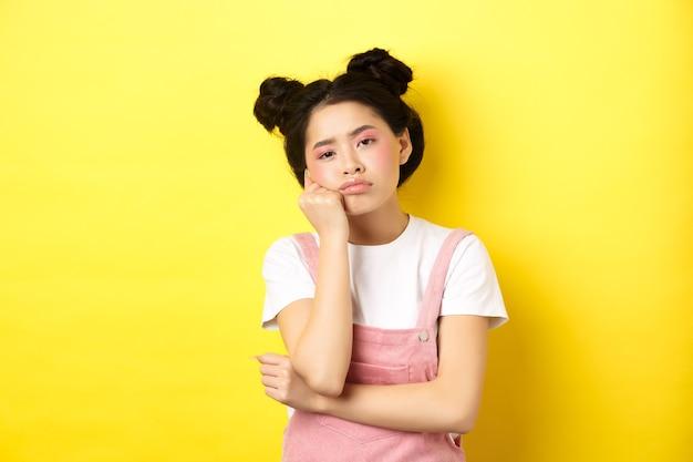 Ragazza asiatica adolescente triste e annoiata in piedi da solo, guardando la telecamera indifferente, fissando con noia, giallo.