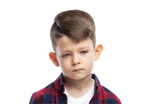 Ragazzo triste di 7 anni. avvicinamento. isolato su una parete bianca