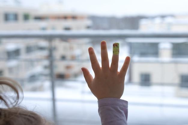 Bambino triste paziente nella finestra dell'ospedale per guardare fuori mettere intonaco fasciato con il dito del palmo vuole andare a casa