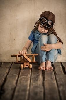 Bambino triste che gioca con un aeroplano di legno giocattolo