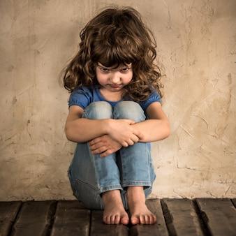 Bambino triste seduto sul pavimento in una stanza buia