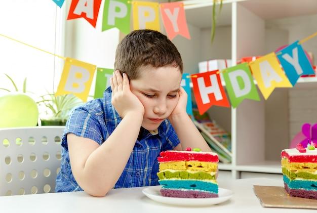 Il bambino triste si siede da solo per il suo compleanno. depressione per mancanza di amici
