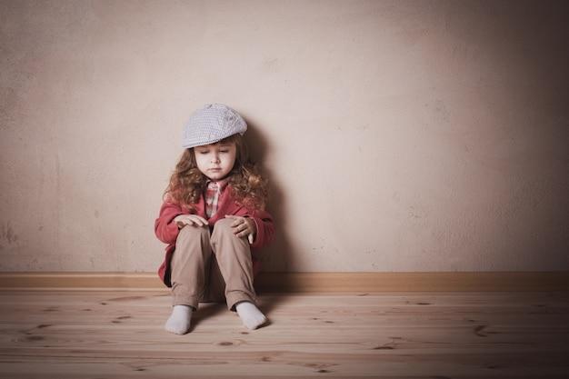 Triste bambino seduto sul pavimento in camera