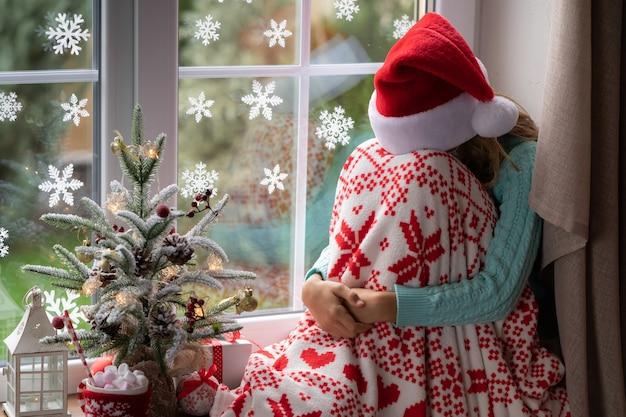Il bambino triste resta a casa nel periodo natalizio. vacanze invernali durante il concetto covid 19 del coronavirus pandemico