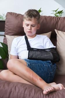 Bambino triste con un braccio rotto nell'ambiente domestico gettato sulla mano del ragazzino