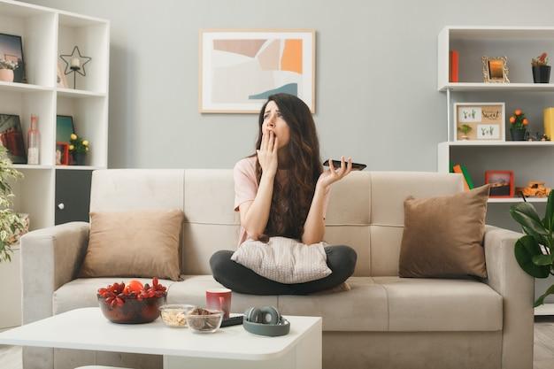 Faccina triste con la mano giovane ragazza che tiene il telefono seduto sul divano dietro il tavolino da caffè nel soggiorno