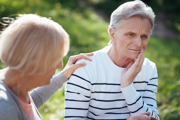 Triste uomo anziano concentrato che si tocca la guancia e soffre di mal di denti mentre sua moglie lo sostiene e si siede sulla panchina all'aperto