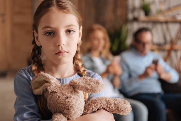 Bambina confusa triste che aspetta l'attenzione dei genitori a casa e tiene il giocattolo mentre gli adulti utilizzano dispositivi e non prestano attenzione