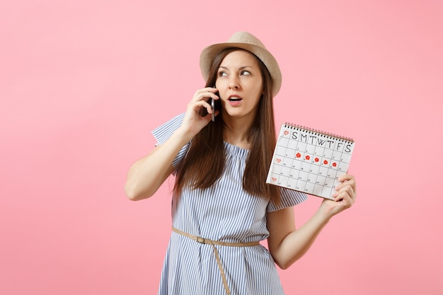 Donna confusa triste che parla al telefono cellulare, tenendo il calendario dei periodi per controllare i giorni delle mestruazioni isolati su sfondo rosa di tendenza brillante. concetto medico, sanitario, ginecologico. copia spazio.