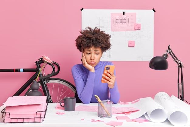 La donna dalla pelle scura triste lavora alla progettazione del progetto ha un'espressione scontenta tiene le pose dello smartphone nello spazio di coworking la scrivania dell'ufficio schizza i progetti intorno. studente infelice della facoltà di architettura