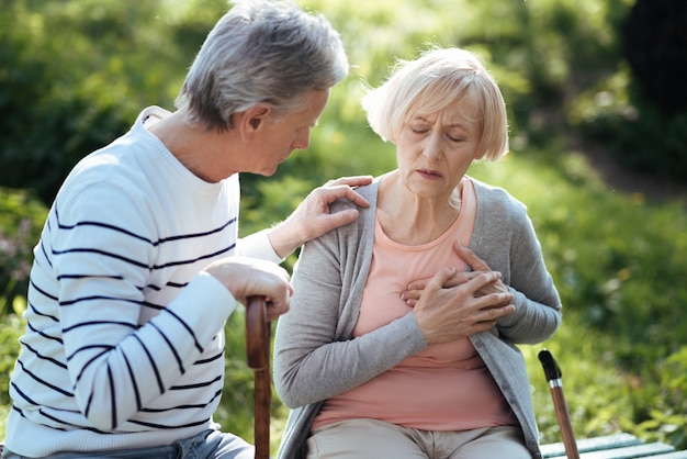 Donna anziana depressa triste che si tocca il petto e ha un attacco di cuore mentre il marito anziano si preoccupa per lei e si siede sulla panchina all'aperto
