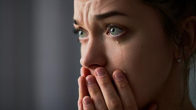 Donna triste piangente disperata pianto con le mani giunte e gli occhi di lacrime durante i guai