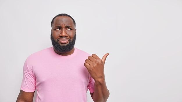 L'uomo barbuto triste dispiaciuto con la pelle scura punta lontano ha un'espressione cupa vestita casualmente si lamenta di qualcosa di ingiusto vestito con una maglietta rosa mostra lo spazio della copia contro il muro bianco