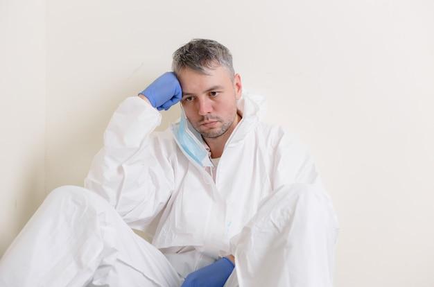 Un triste dottore in tuta protettiva siede per terra nel corridoio dell'ospedale. operatori sanitari durante la pandemia di coronavirus covid19.